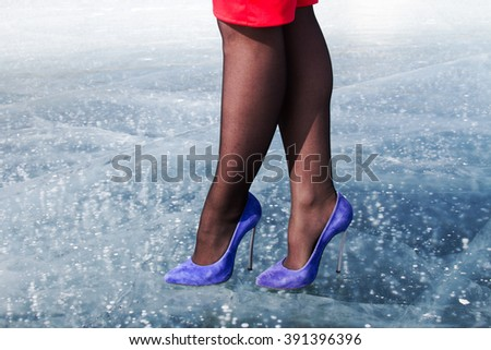 Female feet in shoes with high heels standing on ice