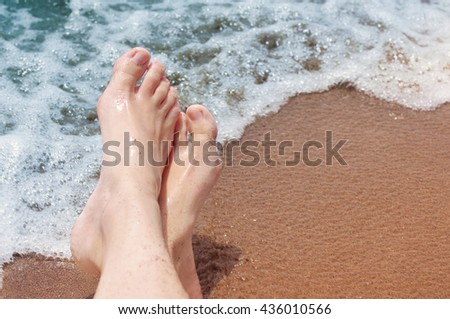 Female feet on a beach against the sea in a summer sunny day. Vacation at the sea - stock photo