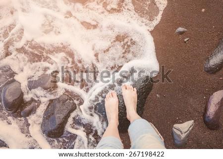 Female feet on a sandy beach. Vintage effect - stock photo