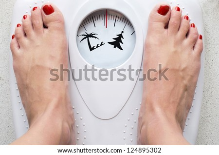 Female feet on bathroom scale with symbols for loosing weight before summer - stock photo