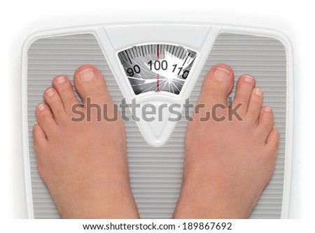 Female feet on broken bathroom scale - stock photo