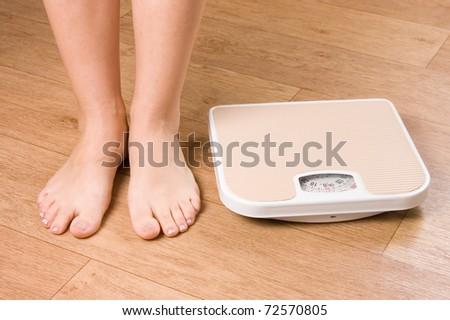 Female feet on scales - stock photo