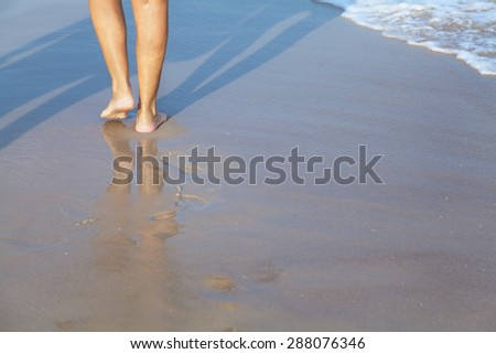 Female feet on the sea beach in wave at summer sunny day