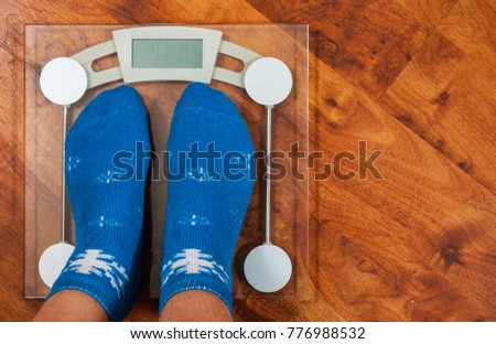 Female feet standing on electronic scales for weight control in Christmas socks on wooden floor background. with copy space. top view