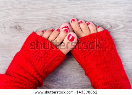 Female feet with color pedicure in red socks - stock photo
