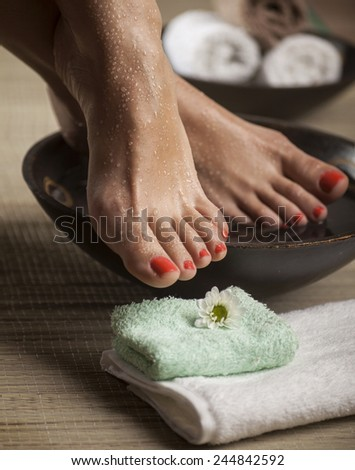 Female feet with drops of water, spa bowls, towels and flowers. - stock photo