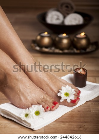 Female feet with drops of water, spa bowls, towels, flowers and candles. - stock photo