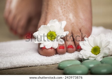 Female feet with drops of water, towel, flowers and spa rocks. Macro image. - stock photo