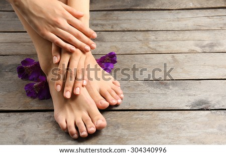 Female feet with flowers on wooden background - stock photo