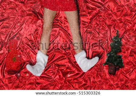 Female feet with snowflakes and Christmas tree on red background