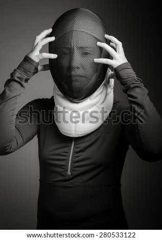 Female fencer in fencing mask looking frustrated - stock photo
