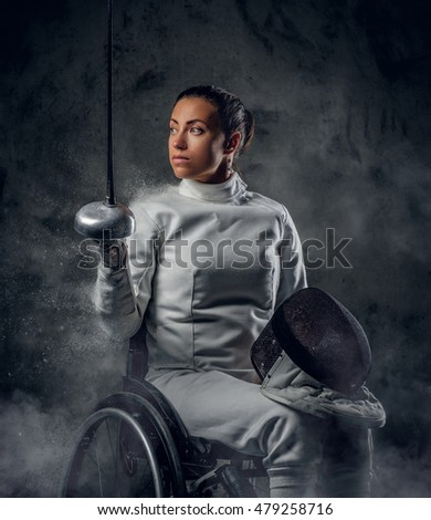Female fencer in wheelchair with safety mask of a face holding rapier, dust effect on image.