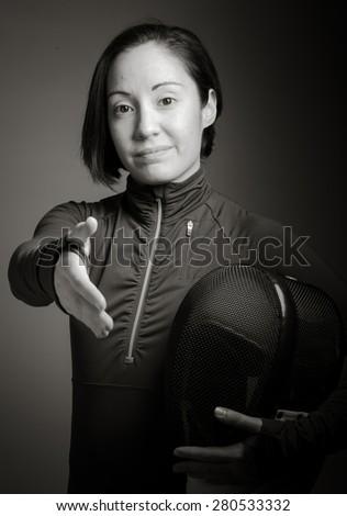 Female fencer offering hand for handshake - stock photo