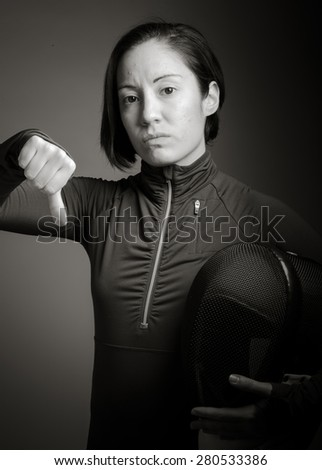 Female fencer showing thumbs down sign - stock photo