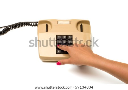 Female finger presses the button on the old phone isolated on white background.