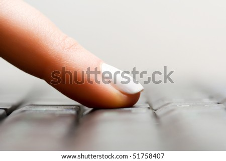 Female finger typing on keyboard. - stock photo