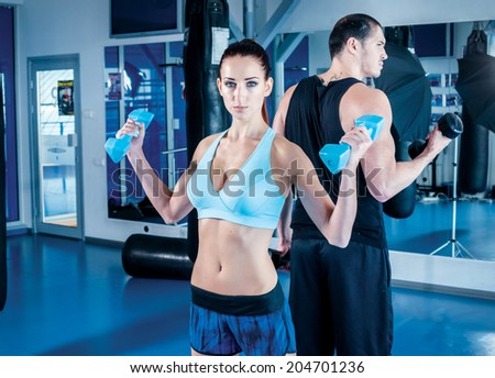 Female fitness athlete looking at the camera and holding a dumbbell. Young couple athletes men and athletes engaged in training with dumbbells and heavy weights.