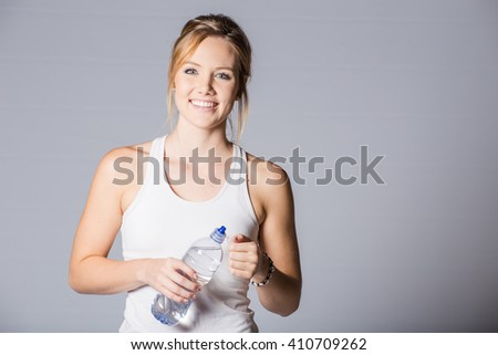 Female fitness model holding a water bottle in a white studio environment on a white background.