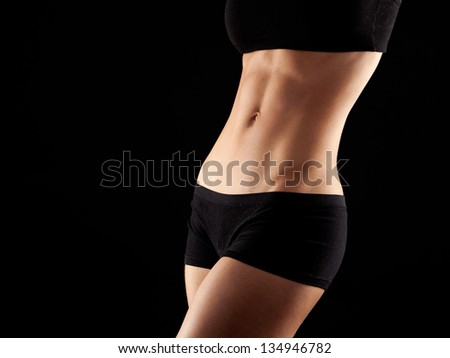 female fitness model posing on black background - stock photo
