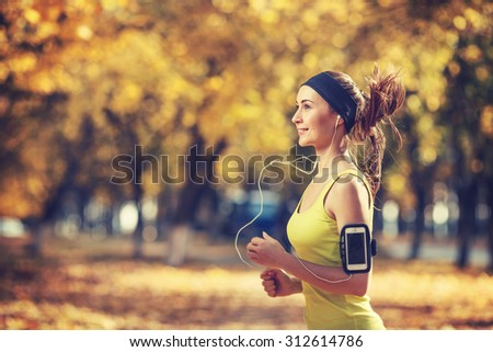 Female fitness model training outside on a warm fall day and listening to music using smart phone. Young woman jogging in autumn park. Sport lifestyle. - stock photo