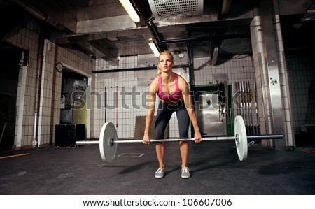 Female fitness performing doing deadlift exercise with weight bar - stock photo