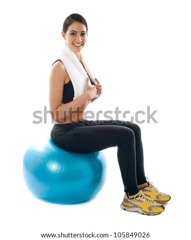Female fitness trainer sitting on ball isolated against white background - stock photo