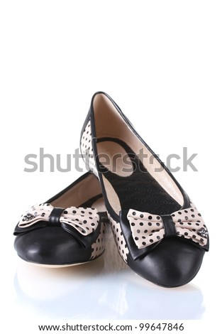 Female flat ballet shoes patterned with black polka dots isolated on white - stock photo