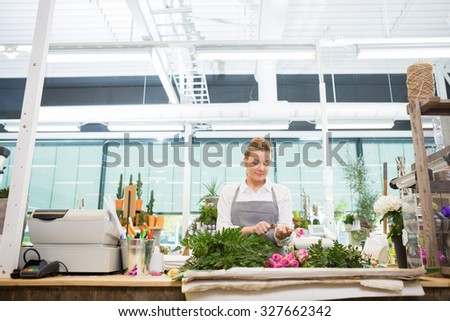 Female florist cutting stem on rose at counter in flower shop - stock photo