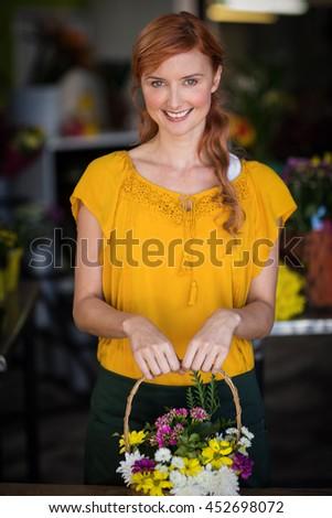Female florist holding basket of flower in the flower shop - stock photo