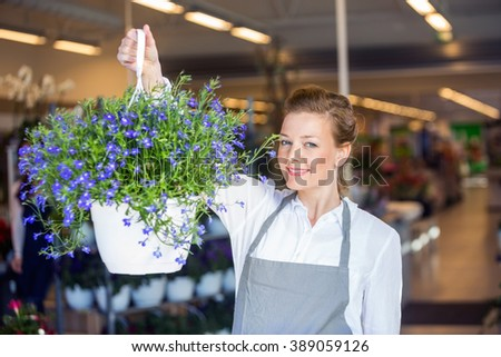 Female Florist Holding Flower Plant In Shop - stock photo