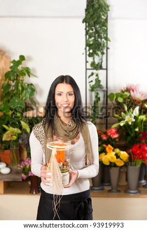 Female florist in flower shop or nursery - stock photo
