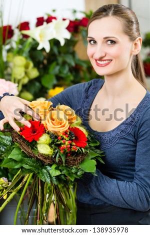 Female florist in flower shop or nursery presenting yellow roses