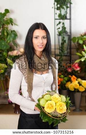 Female florist in flower shop or nursery with yellow roses - stock photo