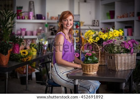 Female florist sitting with basket of flowers in the flower shop - stock photo