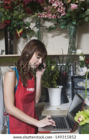 Female florist using laptop and mobile phone in flower shop - stock photo
