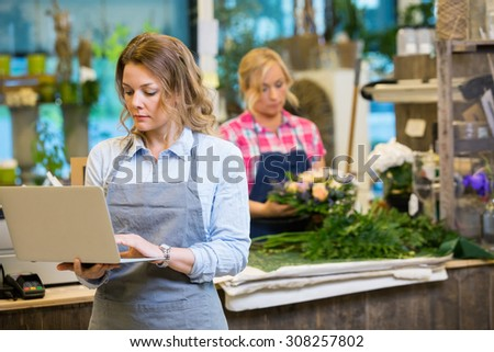 Female florist using laptop with colleague in background at flower shop - stock photo