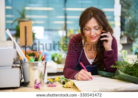 Female florist using mobile phone while writing on paper in flower shop - stock photo