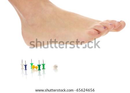 Female foot above pushpin, isolated on white background - stock photo