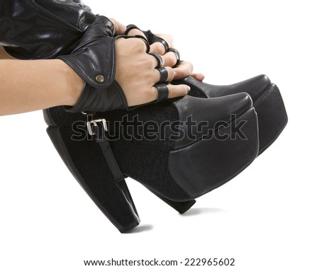 female foot in stylish black heeled leather boots and hands in fashionable gloves (Young fashionable beauty) - stock photo