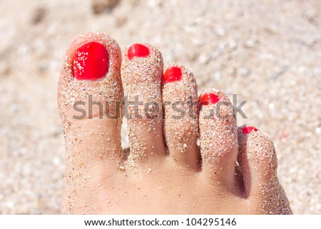 Female foot with red pedicure in beach sand - stock photo