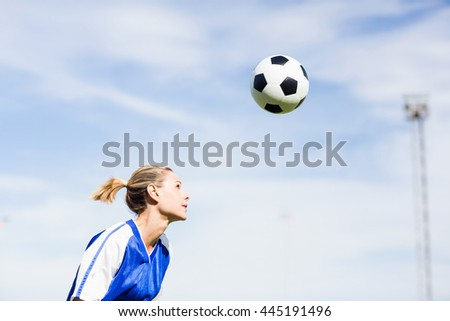 Female football player playing football on football field