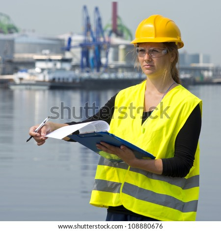 Female foreman turning a page on her clip board during her inspection rounds through an industrial harbor - stock photo