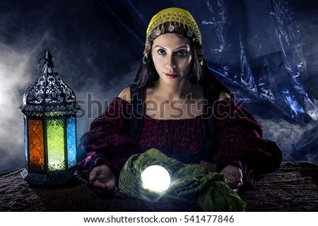 Female fortune teller doing a psychic reading with a cystal ball predicting fate or destiny and the future.  The image depicts religion or the paranormal.