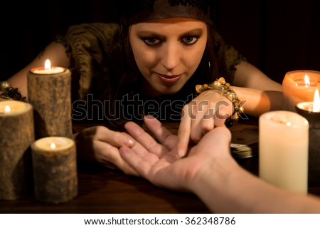 female fortune Teller is reading the lifeline and heart line, concept palmistry - stock photo