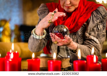 Female Fortuneteller or esoteric Oracle, sees in the future by looking into their crystal ball  - stock photo