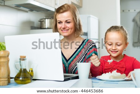 Female freelancer working at notebook, little girl eating nearby