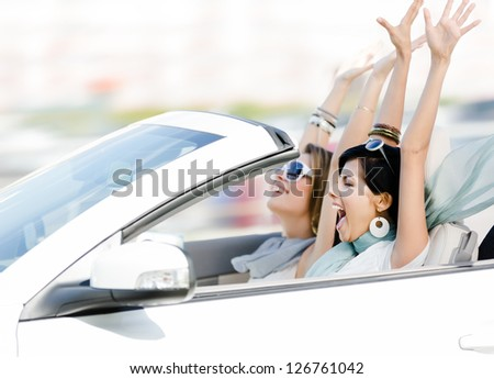 Female friends driving cabriolet with the hands up and having fun on the vacation - stock photo