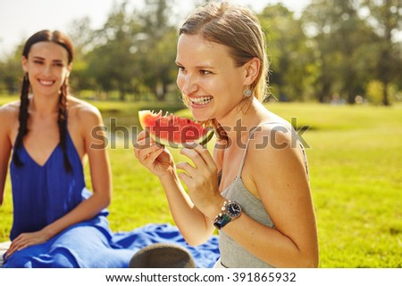 Female friends in the park sitting on the grass in joyful in sunny day and eating watermelon - stock photo