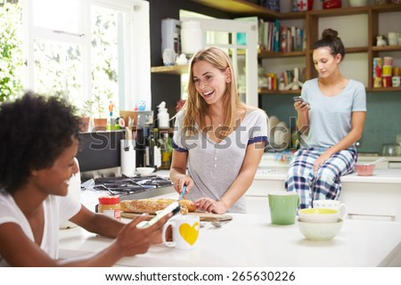 Female Friends Making Breakfast Whilst Checking Mobile Phone - stock photo