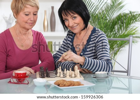Female friends playing chess - stock photo